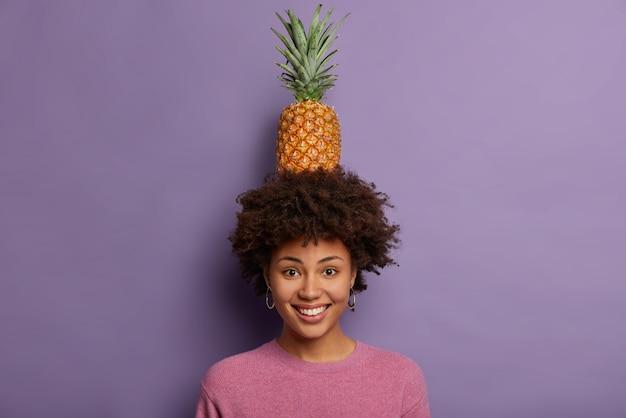 Porträt der attraktiven jungen frau spielt mit reifer ananas, schaut in die kamera, lächelt breit, zeigt weiße zähne, trägt freizeitpullover