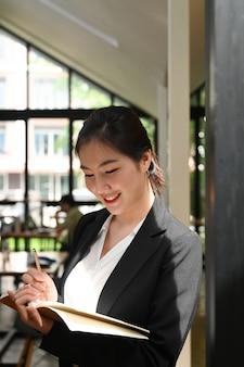 Porträt der attraktiven jungen geschäftsfrau, die auf einem notizblock schreibt und im besprechungsraum steht.