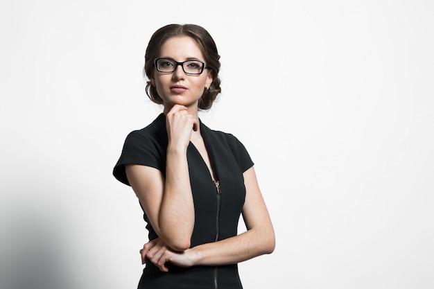 Porträt der attraktiven jungen kaukasischen geschäftsfrau, die hand nahe ihrem kinn auf grau hält