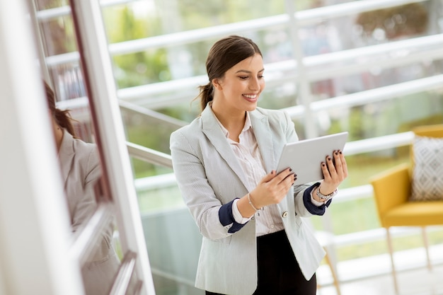Porträt der attraktiven jungen sicher lächelnden und arbeitenden geschäftsfrau