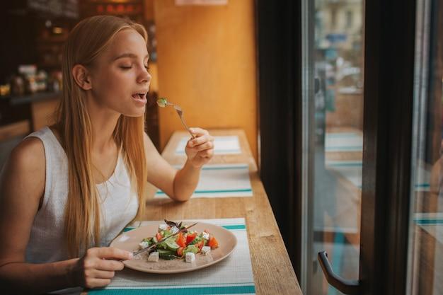 Porträt der attraktiven kaukasischen lächelnden frau, die salat isst