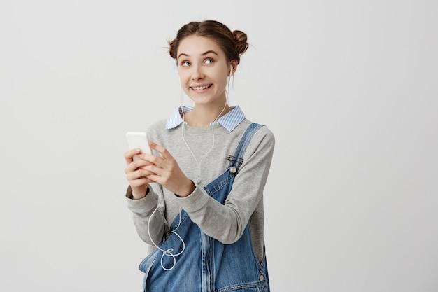 Porträt der attraktiven kindlichen frau im jeansoverall, der mit freudigen gefühlen seitwärts schaut. verliebte frau, die angenehme nachricht auf ihrem smartphone empfängt, das glück fühlt. gesichtsausdrücke