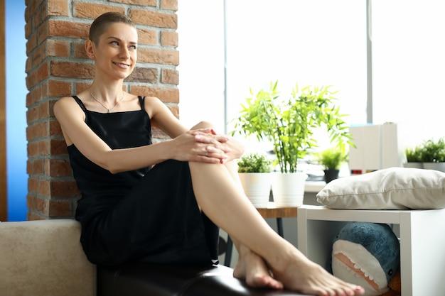 Porträt der attraktiven kurzhaarigen frau, die auf couch sitzt und für bild aufwirft. lächelnde junge frau im einfachen schwarzen kleid im wohnzimmer. modellierungs- und schönheitskonzept