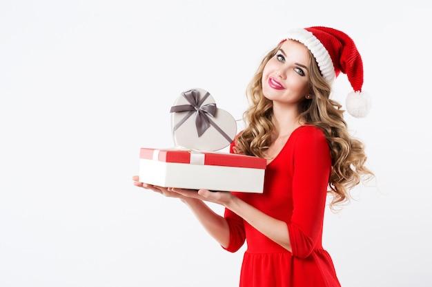 Porträt der attraktiven lächelnden blonden frau im weihnachtsmannhut und im roten kleid