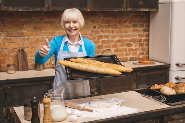 Porträt der attraktiven lächelnden glücklichen älteren älteren frau kocht auf küche. großmutter macht leckeres backen. daumen hoch.