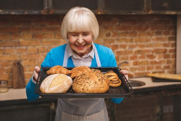 Porträt der attraktiven lächelnden glücklichen älteren älteren frau kocht auf küche. großmutter macht leckeres backen.