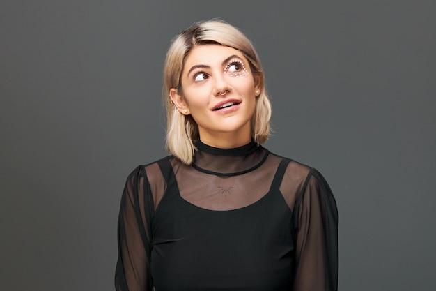 Porträt der attraktiven modischen jungen blonden frau gekleidet in stilvollen kleidern, die isoliert oben schauen mit augen, die interesse und neugier ausdrücken, mund öffnen. menschliche mimik