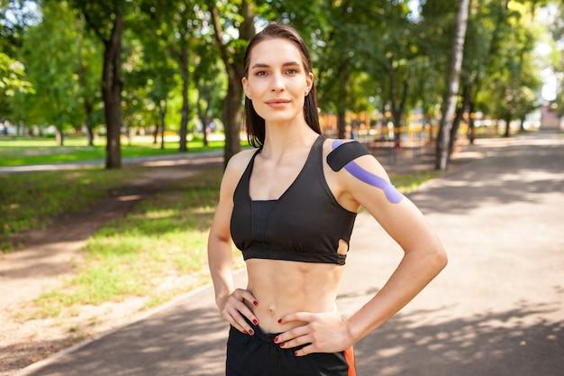 Porträt der attraktiven muskulösen brünetten frau, die schwarzes sportoutfit trägt