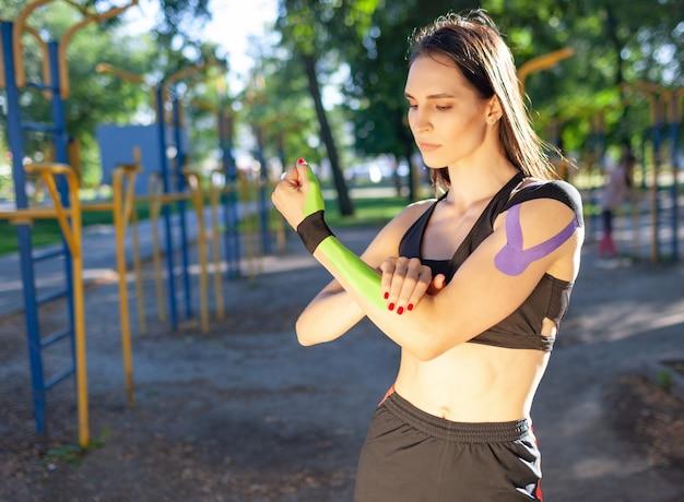 Porträt der attraktiven muskulösen brunettefrau, die schwarzes sportoutfit trägt und beiseite schaut. junge selbstbewusste sportlerin posiert mit verschränkten armen, buntes kinesiotaping auf den armen.