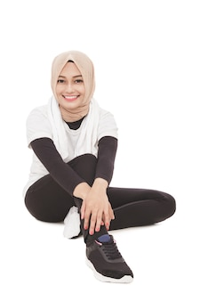 Porträt der attraktiven muslimischen sportlichen frau, die auf dem boden sitzt