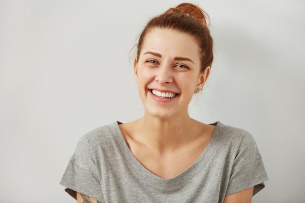 Porträt der attraktiven niedlichen frau, die über graue wand lacht oder lächelt