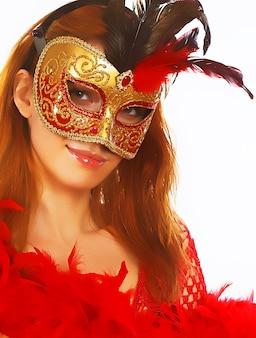 Porträt der attraktiven schönen jungen frau, die goldene karnevalsmaske trägt