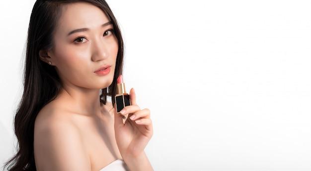 Porträt der attraktiven schönheits-asiatin in mode, die mit lippenstift aufwirft