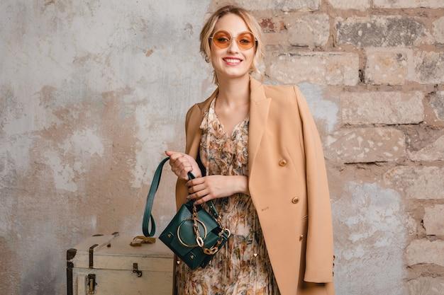 Porträt der attraktiven stilvollen blonden frau im beigen mantel, der in straße gegen weinlesewand geht