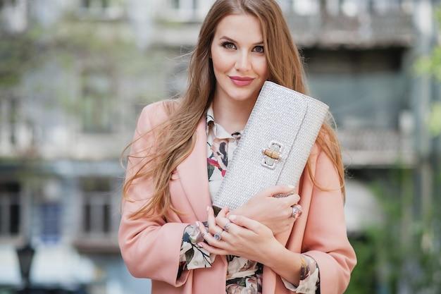 Porträt der attraktiven stilvollen lächelnden frau, die stadtstraße im rosa mantelfrühlingsmodetrend hält geldbörse geht