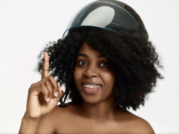 Porträt der attraktiven überraschten afroamerikanerfrau im motorradhelm auf weißer wand. schönheits- und hautschutzkonzept