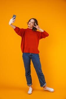 Porträt der aufgeregten emotionalen jungen hübschen frau, die isoliert über gelber wand aufwirft, machen selfie per handy machen friedensgeste.