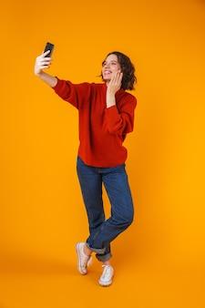 Porträt der aufgeregten emotionalen jungen hübschen frau, die isoliert über gelber wand aufwirft, nehmen selfie per handy.