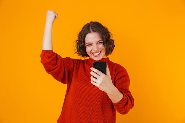 Porträt der aufgeregten emotionalen jungen hübschen frau, die lokal über gelbe wand unter verwendung des mobiltelefons aufwirft.