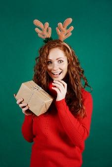 Porträt der aufgeregten frau, die weihnachtsgeschenk öffnet