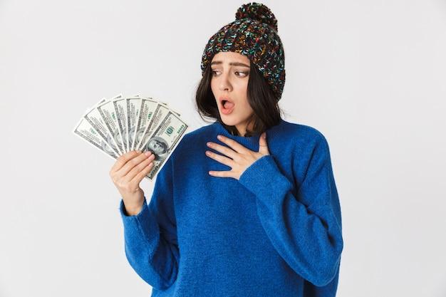 Porträt der aufgeregten frau, die wintermütze hält, die fan des dollargeldes beim stehen hält, lokalisiert auf weiß