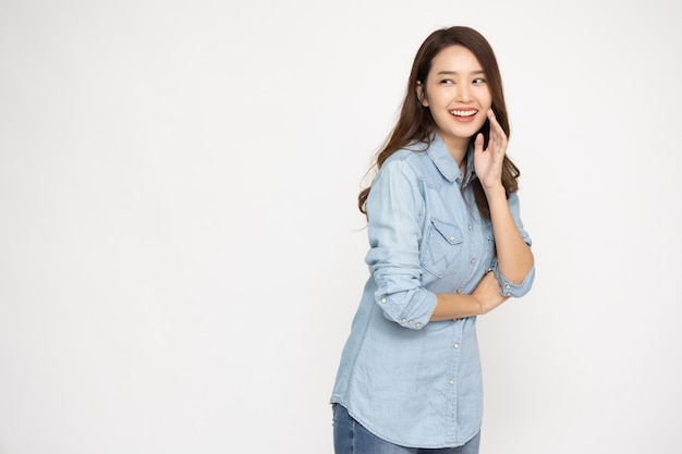 Porträt der aufgeregten glücklichen jungen asiatischen frau, die jeanshemd lokalisiert über weißem hintergrund trägt