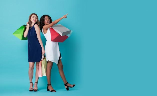 Porträt der aufgeregten hand der jungen frau zwei, die einkaufstasche hält und mit ihrem finger zeigend auf kopienraum über blauem hintergrund