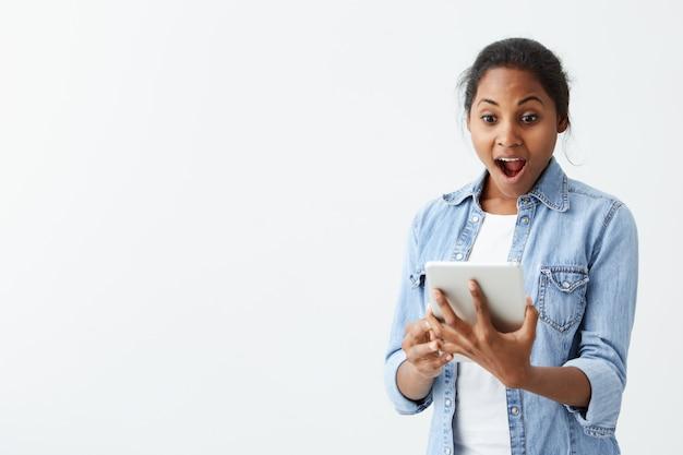 Porträt der aufgeregten jungen afroamerikanischen frau, die vor schock und erstaunen schreit und neue tablette in ihren händen hält. überraschtes, dunkelhäutiges mädchen mit käferaugen, das beeindruckt aussieht, kann ihren eigenen augen nicht trauen