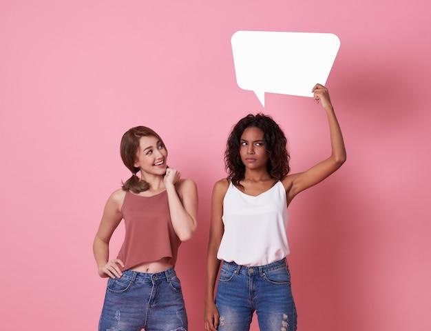 Porträt der aufgeregten jungen frau zwei, die leere spracheblase hält und machen ein gesicht denkend auf rosa.