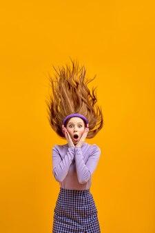 Porträt der aufgeregten kaukasischen rothaarigefrau mit haarfliegen beim hören von musik in kopfhörern, lieder singen. hübsche emotionale dame in freizeitkleidung unter schock durch musik, händchen haltend auf wangen