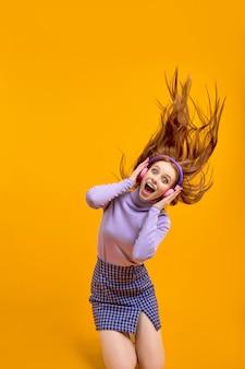 Porträt der aufgeregten kaukasischen rothaarigefrau mit haarfliegen beim hören von musik in kopfhörern, lieder singen. hübsche emotionale dame in freizeitkleidung unter schock durch musik