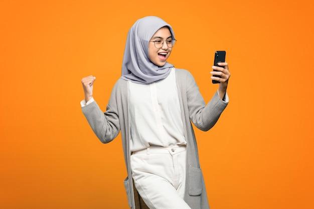 Porträt der aufgeregten schönen asiatischen frau beim betrachten des smartphones