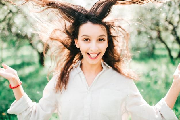 Porträt der ausdrucksstarken lustigen brünetten frau mit ihren haaren in der luft, die im smaragdgarten aufwirft