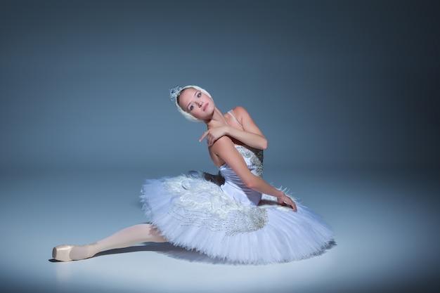 Porträt der ballerina in der rolle eines weißen schwans auf blauem hintergrund