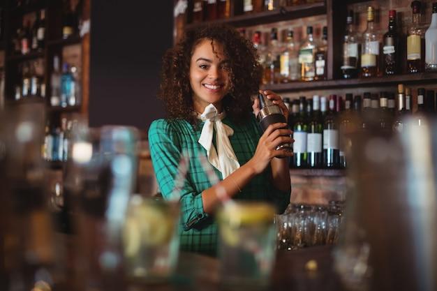 Porträt der barkeeperin, die ein cocktailgetränk im cocktail-shaker mischt