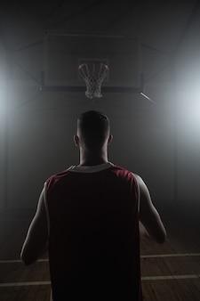 Porträt der basketballspielerfront die rückseite vor einem korb