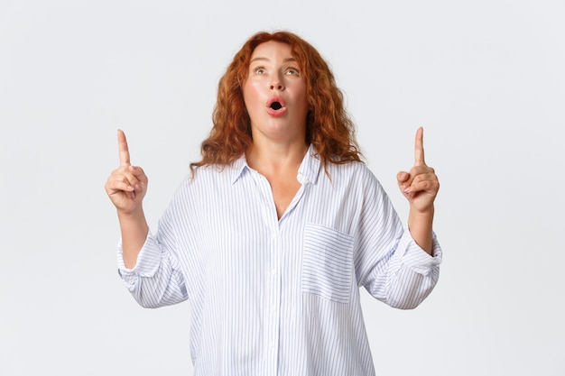 Porträt der beeindruckten keuchenden rothaarigen frau, die nach luft schnappte, wunderte sich, offener mund fasziniert, wow sagend, finger schauend und finger auf superangebot zeigend, banner mit werbung zeigend.