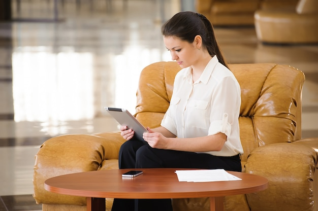 Porträt der beschäftigten arbeitenden geschäftsfrau beim sitzen am sofa