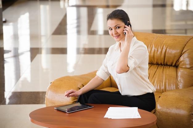 Porträt der beschäftigten geschäftsfrau, die auf ipad beim sitzen am sofa arbeitet. kleinbetrieb.