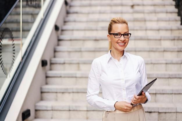 Porträt der beschäftigten schönen lächelnden positiven modischen geschäftsfrau, die tablette im freien hält