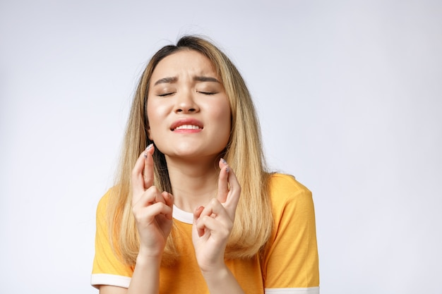 Porträt der betenden jungen frau, die freizeitkleidung trägt, die gott bettelt, bitte schauen sie mit den fingern nach oben