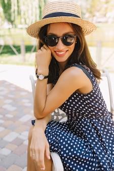 Porträt der bezaubernden artfrau im sommerpark, der sommerhut und schwarze sonnenbrille und niedliches kleid trägt.