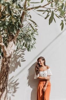 Porträt der bezaubernden dame im sommerresort-outfit, das neben olivenbaum auf weißer wand aufwirft