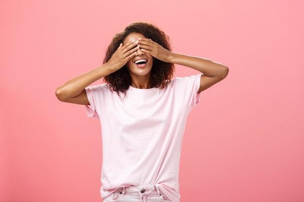 Porträt der bezaubernden freudigen dunkelhäutigen verspielten frau mit dem lockigen haar im t-shirt, das augen schließt und zehn mit breitem glücklichem lächeln zählt, das versteckspiel spielt oder auf überraschung über rosa wand wartet