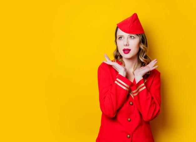 Porträt der bezaubernden vintagen stewardess, die in der roten uniform trägt. auf gelbem hintergrund isoliert.