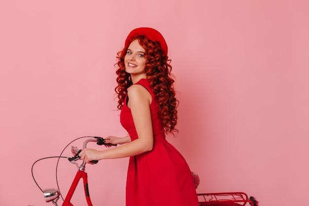 Porträt der blauäugigen attraktiven frau in der roten baskenmütze. rothaariges mädchen im kleid, das mit fahrrad auf rosa raum aufwirft.
