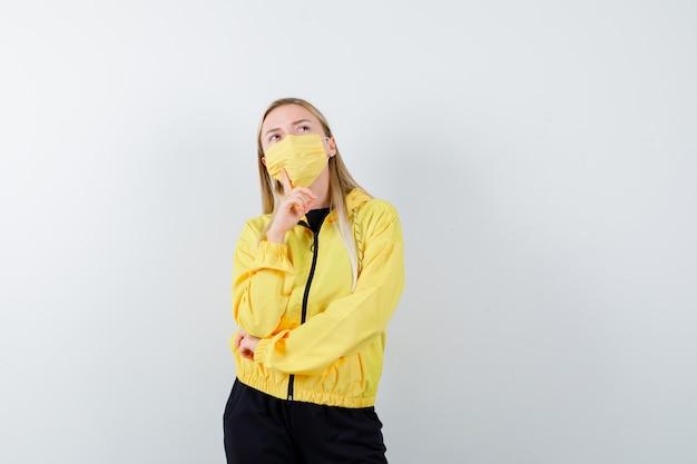 Porträt der blonden dame, die finger nahe mund im trainingsanzug, in der maske und in der nachdenklichen vorderansicht hält