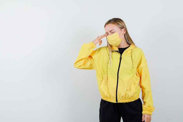 Porträt der blonden dame, die sich mit handfeuerwaffe im trainingsanzug, in der maske und in der deprimierten vorderansicht schießt