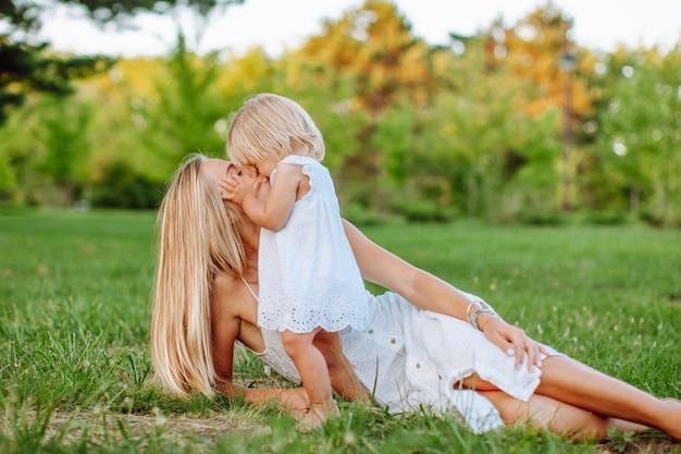 Porträt der blonden frau, die ihre kleine tochter umarmt, die auf einem grünen gras im sommerpark liegt. mädchen tragen weiße kleider, familienblick.
