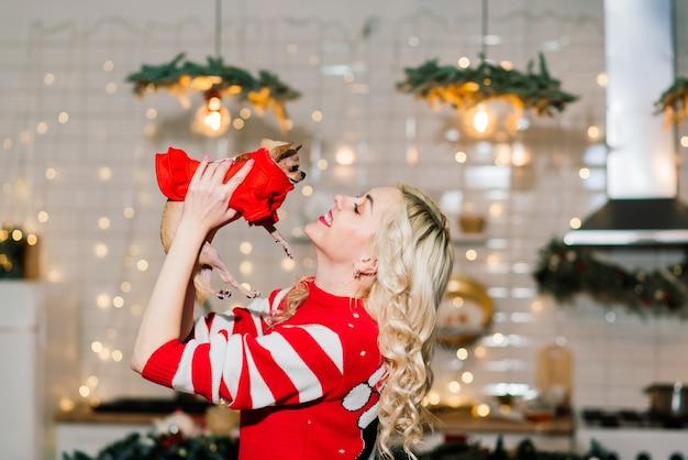 Porträt der blonden frau, die weihnachts-weihnachtsmann hält, der chihuahua-hunde im weihnachtskostüm in der küche mit weihnachtsdekoration hält, lächelt und kamera betrachtet.